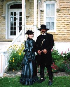 [Photo: 'Josephine and Wyatt S. Earp' (Terrie and James George) in front of 1890s-style Mueller-Schmidt garden.]
